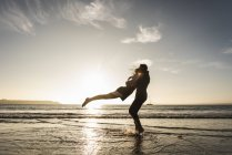 France, Brittany, happy young couple hugging on the beach at sunset — Stock Photo