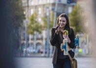 Усміхнена молода жінка з Longboard і закускою в місті за допомогою мобільного телефону — стокове фото