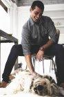 Молодой человек сидит за столом и гладит собаку. — стоковое фото
