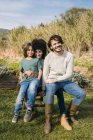 Happy family sitting on a bench in a garden — Stock Photo