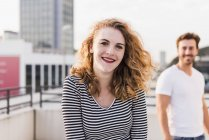 Portrait of happy young woman with boyfriend in the background at sunset — Stock Photo