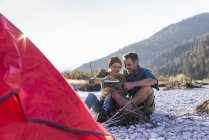 Mature couple camping at riverside in the evening light — стоковое фото