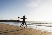 Франция, Британия, счастливая молодая пара, прыгающая на пляже на закате — стоковое фото