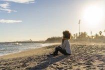 Жінка сидить на пляжі після заходу сонця. — стокове фото