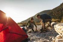 Pares maduros que acampam no beira-rio com madeira para um incêndio do acampamento — Fotografia de Stock