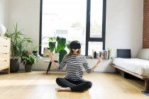 Jovem em casa vestindo óculos VR e fazendo ioga — Fotografia de Stock