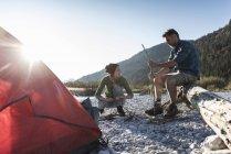 Pares maduros que acampam no beira-rio, com madeira para um incêndio do acampamento — Fotografia de Stock