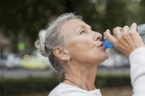 Donna anziana all'aperto acqua potabile dalla bottiglia — Foto stock