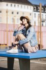 Relaxed young woman sitting on tennis table and listening to music — Stock Photo