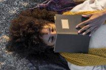 Женщина лежит на песке, отдыхает на пляже, читает бук — стоковое фото