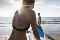 France, Brittany, young couple carrying paddleboard at the sea together — Stock Photo