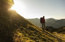 Femme debout dans les montagnes, profitant de la vue — Photo de stock
