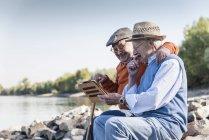 Due vecchi amici seduti lungo il fiume, utilizzando tablet digitale — Foto stock