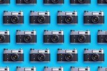 Фотокамеры, расположенные в ряд на синем фоне — стоковое фото