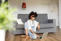 Кузнечиха сидит дома с наушниками и ноутбуком — стоковое фото
