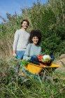 Woman sitting in wheelbarrow, holding fresh vegetables, man pushing her — Stock Photo