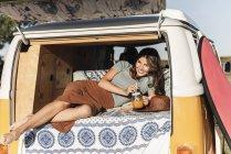 Hübsche Frau auf einem Roadtrip mit ihrem Wohnmobil, macht eine Pause, trinkt Saft — Stockfoto