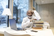 Portrait of smiling mature man sitting at desk with laptop and stack of books — Stock Photo