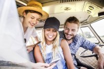 Happy friends inside van looking at smartphone — Stock Photo