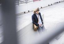 Giovane uomo d'affari con skateboard, appoggiato al muro, utilizzando lo smartphone — Foto stock