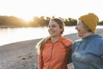 Fit grandmother and granddaughter walking at the river with arms around, having fun — Stock Photo