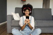 Кузнечиха сидела дома с наушниками и мобильным телефоном — стоковое фото