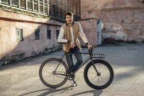 Joven con bicicleta fixie de cercanías en un patio trasero de la ciudad - foto de stock