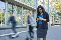 Businesswoman using cell phone with commuters riding on scooters — Stock Photo
