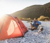 Reife Mann Camping am Flussufer, mit Tablet — Stockfoto