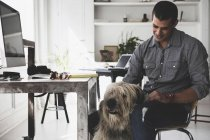 Young man sitting at desk stroking dog — Stock Photo