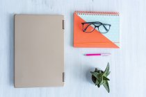 Laptop, notebook and spectackes on a desk, flat lay — Stock Photo