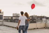 Back view of young couple on roof terrace at evening twilight — Stock Photo