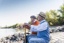 Zwei alte Freunde sitzen auf einem Baumstamm und beobachten den Fluss — Stockfoto