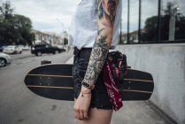 Close-up of young woman holding carver skateboard on the pavement — Stock Photo