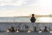Испания, Барселона, вид сзади женщины, сидящей на стене перед морем — стоковое фото