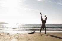 França, Bretanha, jovem fazendo um suporte de mão na praia ao lado da prancha de surf — Fotografia de Stock