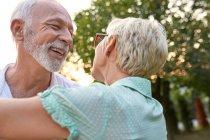 Счастливая пожилая пара обнимается на улице — стоковое фото