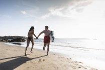 Francia, Bretaña, joven pareja con tabla de surf corriendo de la mano en el mar - foto de stock