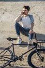 Молодий чоловік з приміського велосипеда fixie сидять на бетонній стіні і говорити на стільниковий телефон — стокове фото