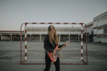 Портрет щасливої молодої жінки, що грає на гітарі на спортивному полі. — стокове фото
