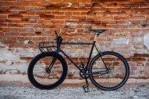 Bicicleta fija de viajero personalizada en la pared de ladrillo - foto de stock