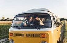 Glückliches Paar sitzt im Wohnmobil und küsst sich — Stockfoto