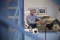 Бізнесмен сидить в офісі і працює на ноутбуку. — стокове фото