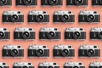 Cámaras de fotos organizadas en fila sobre el fondo de color coral - foto de stock