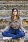 Jeune femme assise dehors dans les escaliers faisant du yoga — Photo de stock