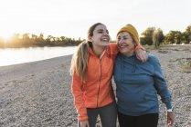 Вписатися бабуся і внучка ходіння по річці з обіймами навколо, веселяться — стокове фото