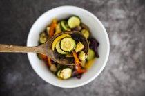 Смесь вареных овощей в миске, на ложке, крупным планом — стоковое фото