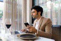 Uomo seduto a tavola in un ristorante, utilizzando laptop e cellulare — Foto stock