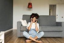 Счастливая женщина сидит дома с наушниками — стоковое фото