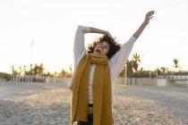 Happy woman having fun on the beach at sunset — Stock Photo